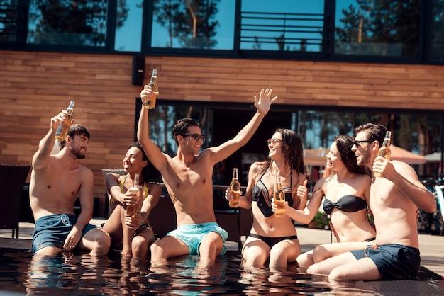 幸せな友達がアルコールでプールパーティーを楽しんでいます。 Premium写真