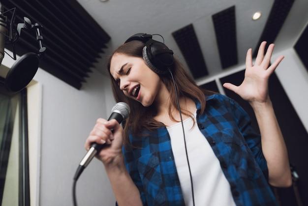 少女は現代のレコーディングスタジオで彼女の歌を歌う Premium写真