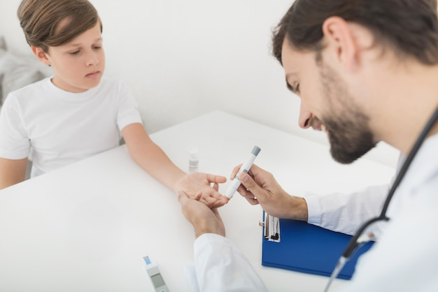 医者は砂糖のためにそれをチェックするために男の子から血液サンプルを取ります Premium写真