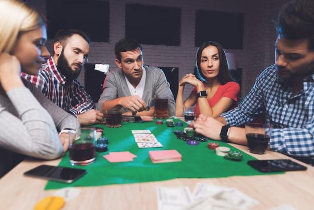 男はカードを見て、誰もが彼が賭けるのを待っています Premium写真