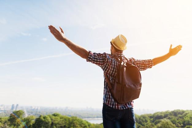 Человек с вытянутыми руками на фоне красивых зеленых пейзажей Premium Фотографии