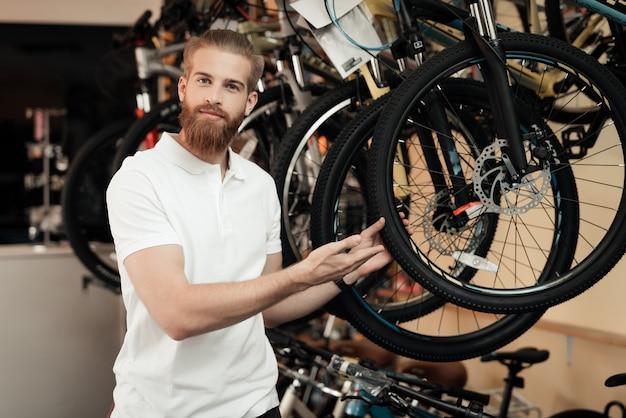 自転車屋の店員が自転車の近くでポーズします。 Premium写真