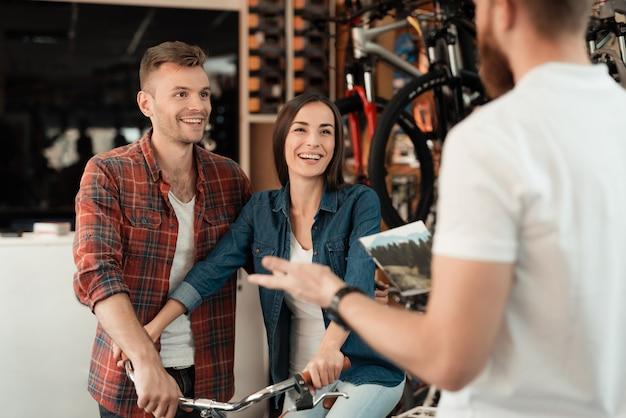 カップルが新しい自転車を選ぶために自転車屋にやって来た Premium写真