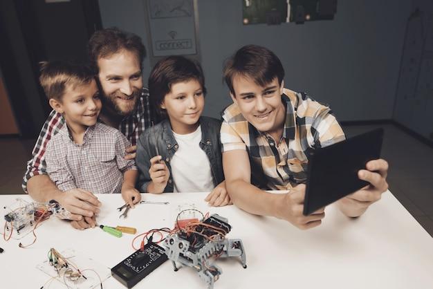 Мальчики-подростки и взрослый мужчина делают селфи на черном планшете Premium Фотографии