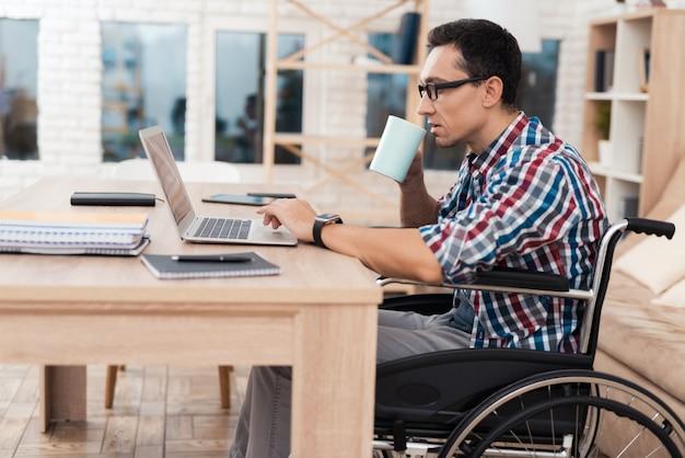 障害者の若者が自宅でノートパソコンで動作します。 Premium写真