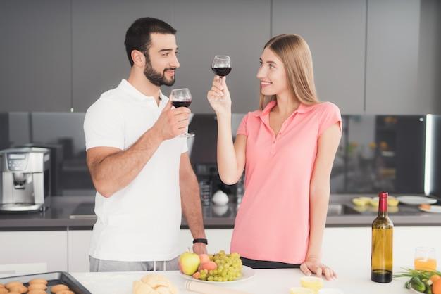 男と女が台所でワインを飲んでいます。 Premium写真