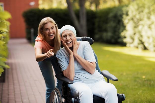 Женщина с раком сидит в инвалидной коляске Premium Фотографии