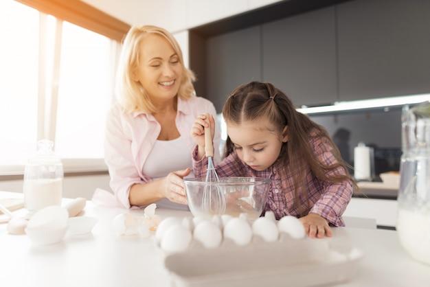 小さな女の子が泡立て器で卵を打っています Premium写真