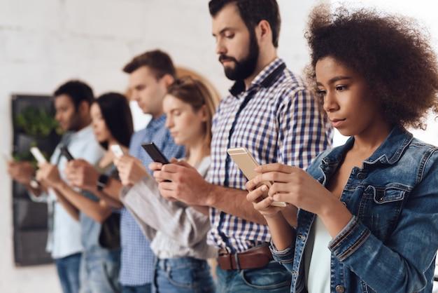 若い人たちは携帯電話に沿って立っています。 Premium写真