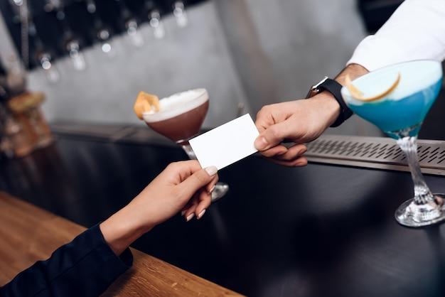 女の子は注文のバーテンダーに支払います。 Premium写真