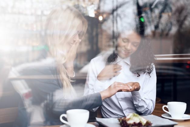 少女とムラートはカフェに座ってコーヒーを飲みます。 Premium写真