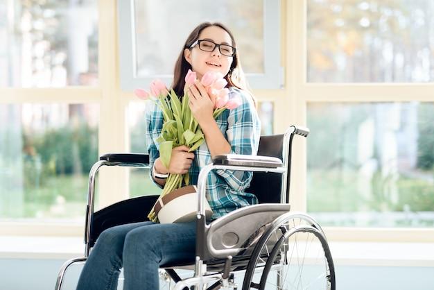彼女の手に花を持つ車椅子の少女。 Premium写真