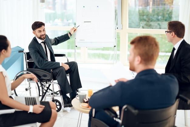 Человек в инвалидной коляске указывает на график на доске. Premium Фотографии