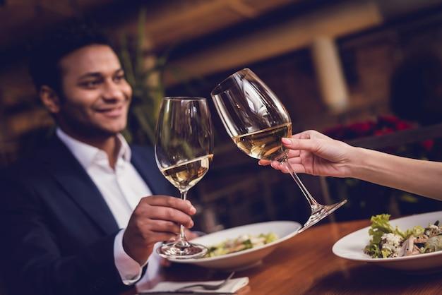 男と女がレストランでデートにワインを飲んでいます。 Premium写真