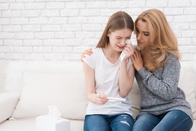 Мать возле расстроен дочь с тестом на беременность. Premium Фотографии