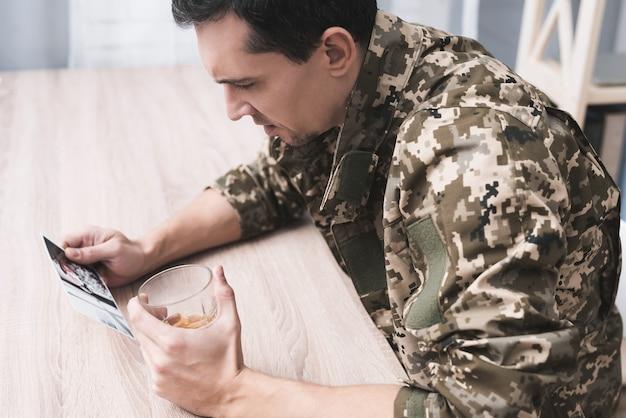 アルコールのガラスと軍人の写真を持つ男。 Premium写真