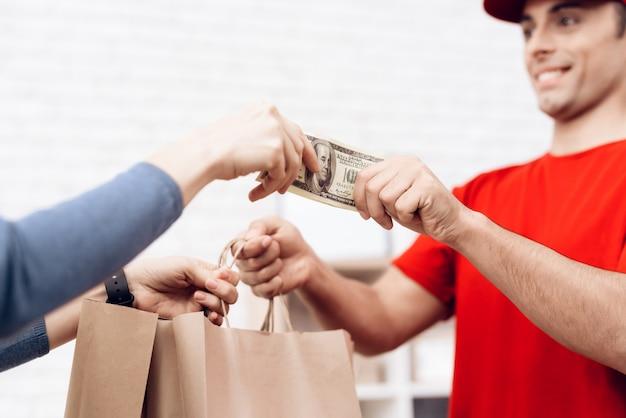 Женщина вручает деньги для доставщика пиццы. Premium Фотографии