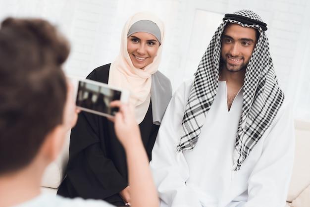 彼のお母さんとお父さんを撮影している小さな男の子。 Premium写真