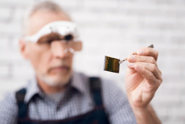 老人は特別なメガネを通してプロセッサを見ます。 Premium写真