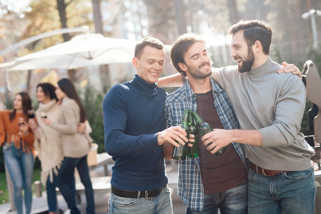 男性は友達とピクニック中にビールを飲みます。 Premium写真