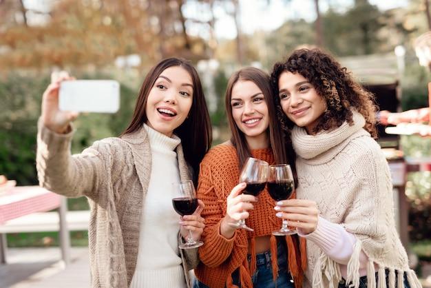 女性は友達とピクニック中に自分撮りをします。 Premium写真