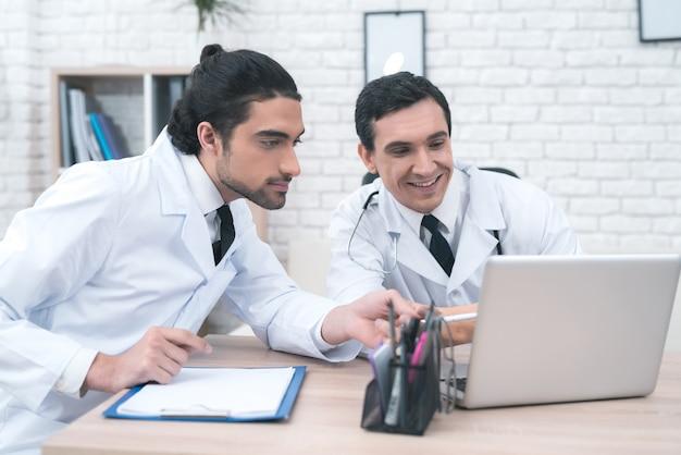 Два доктора смотрят на что-то на ноутбуке. Premium Фотографии