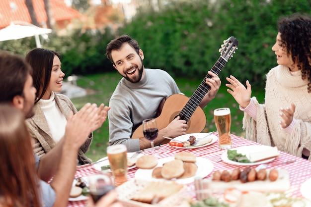 友達は楽しんで、食べ物を作ったり、アルコールを飲みます。 Premium写真