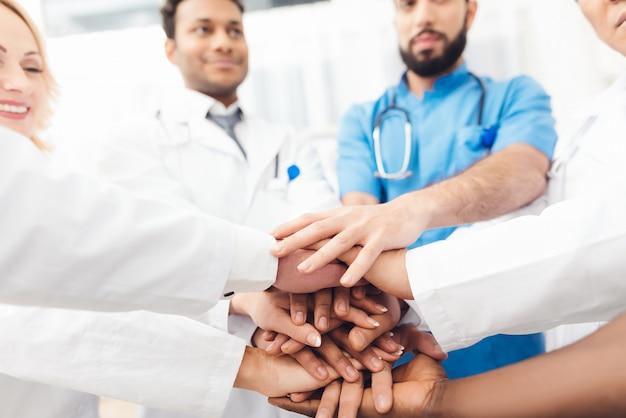 医師のグループがお互いの手を握っています。 Premium写真