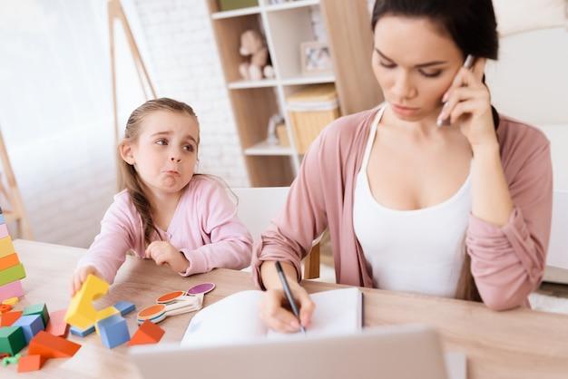電話で話している間、小さな女の子は彼女の母親を逃します Premium写真