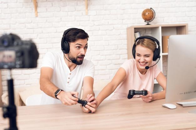 男と女のポッドキャスターは、ポッドキャスト用のビデオゲームをプレイします。 Premium写真