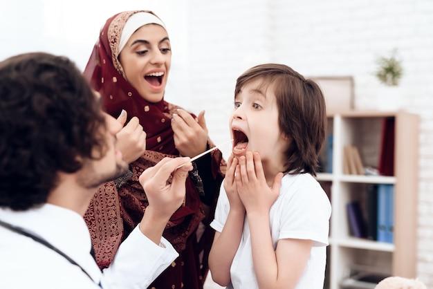 アラブの医者が小さな男の子を診断します。 Premium写真