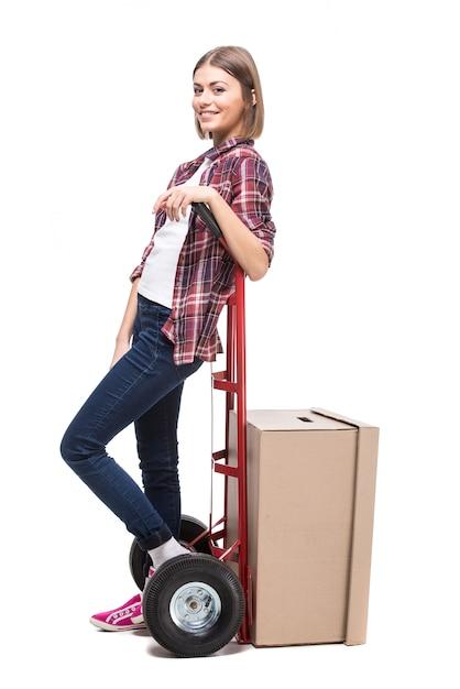 紙箱と手押し車を持つ若い女性。 Premium写真