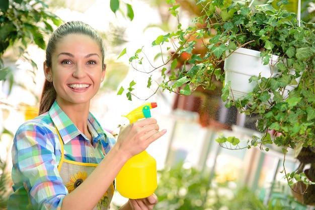 温室で働く若い笑顔の女性花屋。 Premium写真
