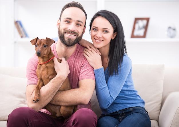 彼らの犬と美しい若いカップル。 Premium写真