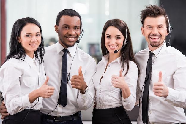 コールセンターの労働者は笑顔でカメラを見ています。 Premium写真