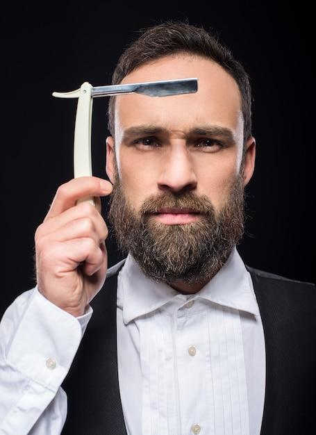 まっすぐなかみそりを持つ若い残忍なひげを生やした男の肖像画。 Premium写真
