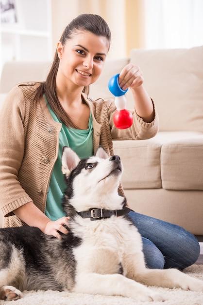 幸せな女は家で彼女の犬と遊んでいます。 Premium写真