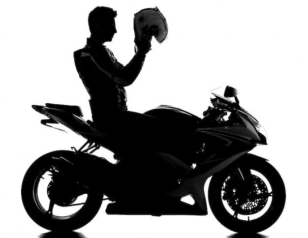 ヘルメットとオートバイレーサーのシルエット。 Premium写真