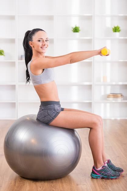女の子がフィットネスボールの上に座って運動を行います。 Premium写真