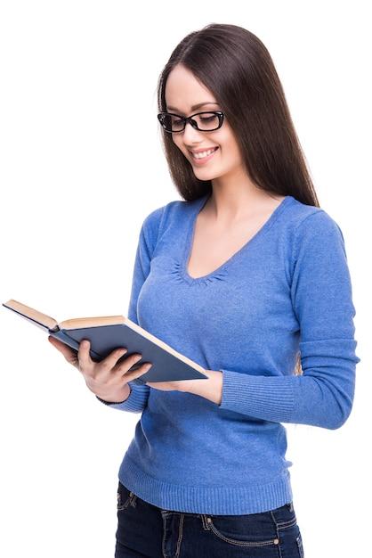 教科書を保持しているメガネでスマート美しい学生少女。 Premium写真