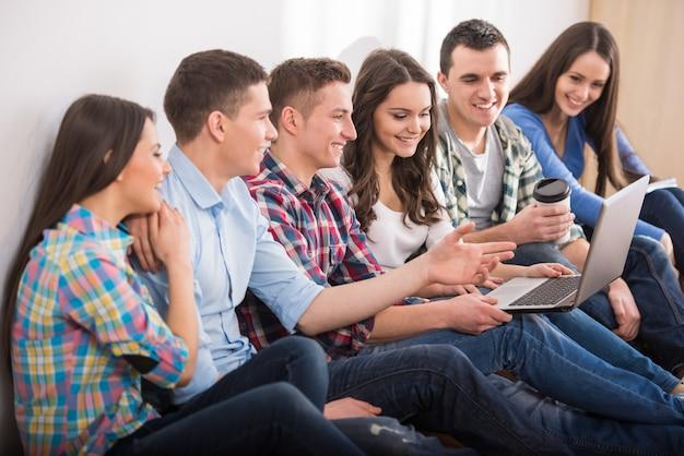 Группа студентов с ноутбуком смотрят что-то. Premium Фотографии