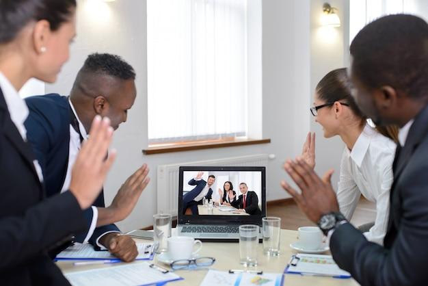 Люди смотрят онлайн-конференцию на экране компьютера. Premium Фотографии