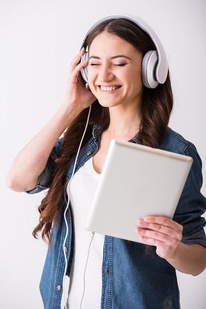 女性はタブレットとヘッドフォンで音楽を聴いています。 Premium写真
