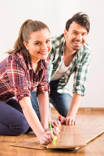 若いカップルは部屋にラミネートフローリングをインストールしています。 Premium写真