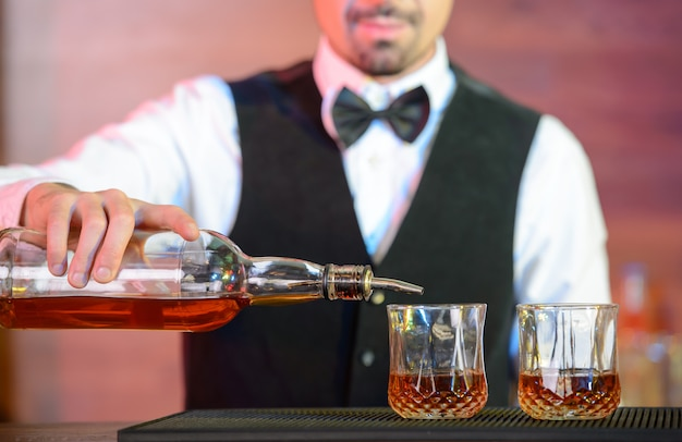 男はバーでグラスにアルコールを注ぎます。 Premium写真