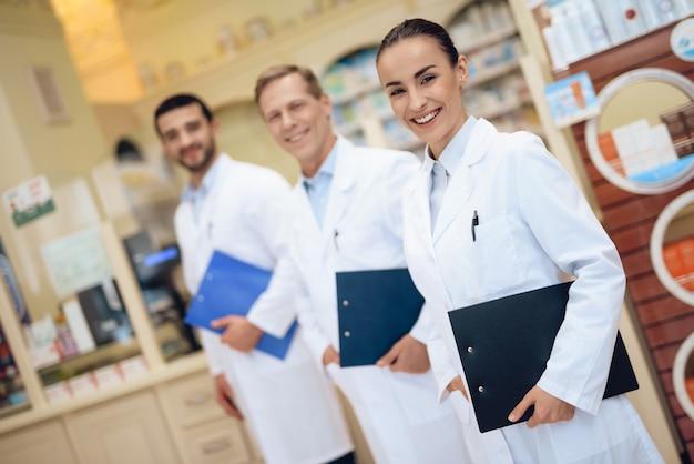 Аптекари стоят в аптеке и держат папку с бумагами Premium Фотографии