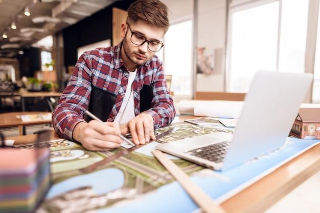 フリーランサー男が机に座ってラップトップで計画を描きます。 Premium写真
