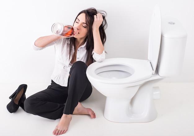 トイレでアルコールを飲むうつ病の若い女性。 Premium写真