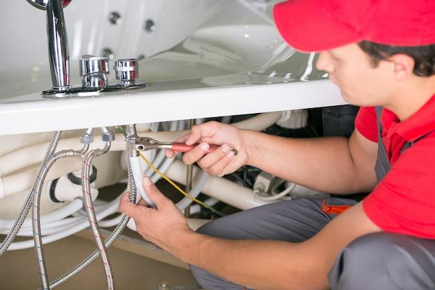男性の配管工は浴室でシンクパイプを固定します。 Premium写真
