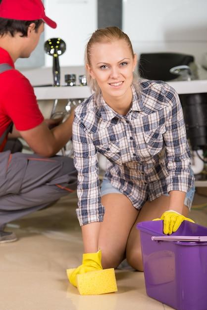 素敵な女性が浴室の床を掃除しています。 Premium写真